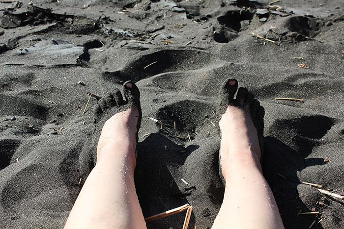 Meine Füße in schwarzem Sand